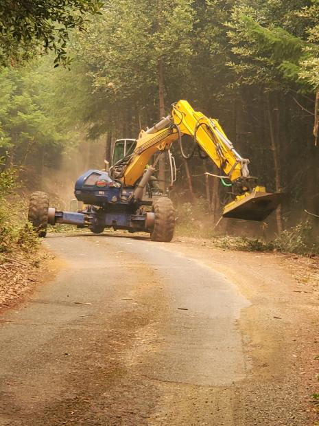 A piece of heavy equipment with a masticator attachment on from mows brush off the side of a gravel road.