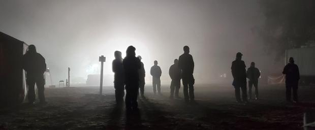 People stand outside in fog and morning darkness.