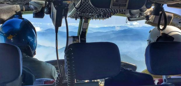 A view from the rear seat of helicopter, forward over the shoulders of the two pilots, with mountains ahead.