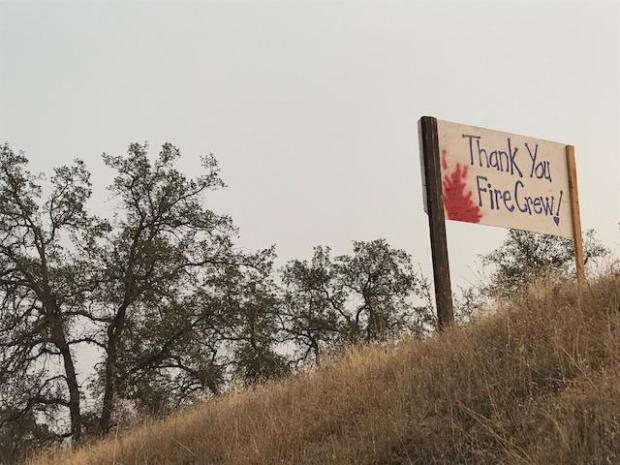 View of a 'thanks fire crews' sign with red painted flames, on a hillside along Hwy 168..