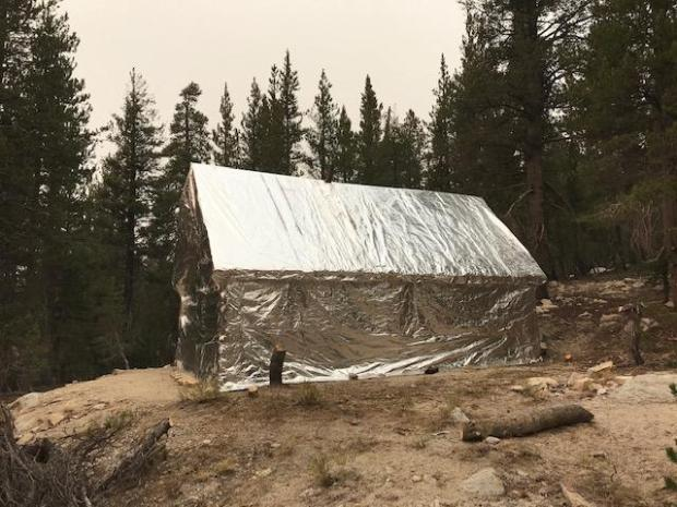 View of a house wrapped in shiny foil to protect it from wildfire heat.