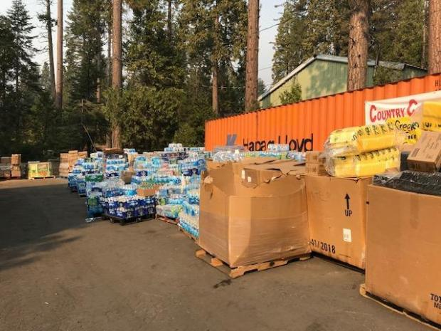 View of stacks of bottled water and boxed food at a public donation site.