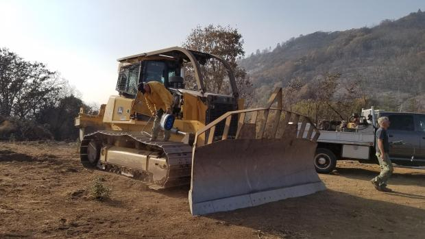 End of shift. Bulldozer maintenance, blowing out air filters after a dusty day of suppression repair. Photo by Dave Stone/USFS