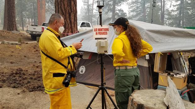 NY Times photojournalist interviewing Air Resource Advisor at Vermillion Camp Ground by Edison Lake, which is also being used as a spike camp by fire resources, about smoke monitoring. Photo by Dave Stone/USFS