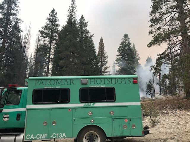 Side view of Palomar Hotshots truck with smoke in the background.