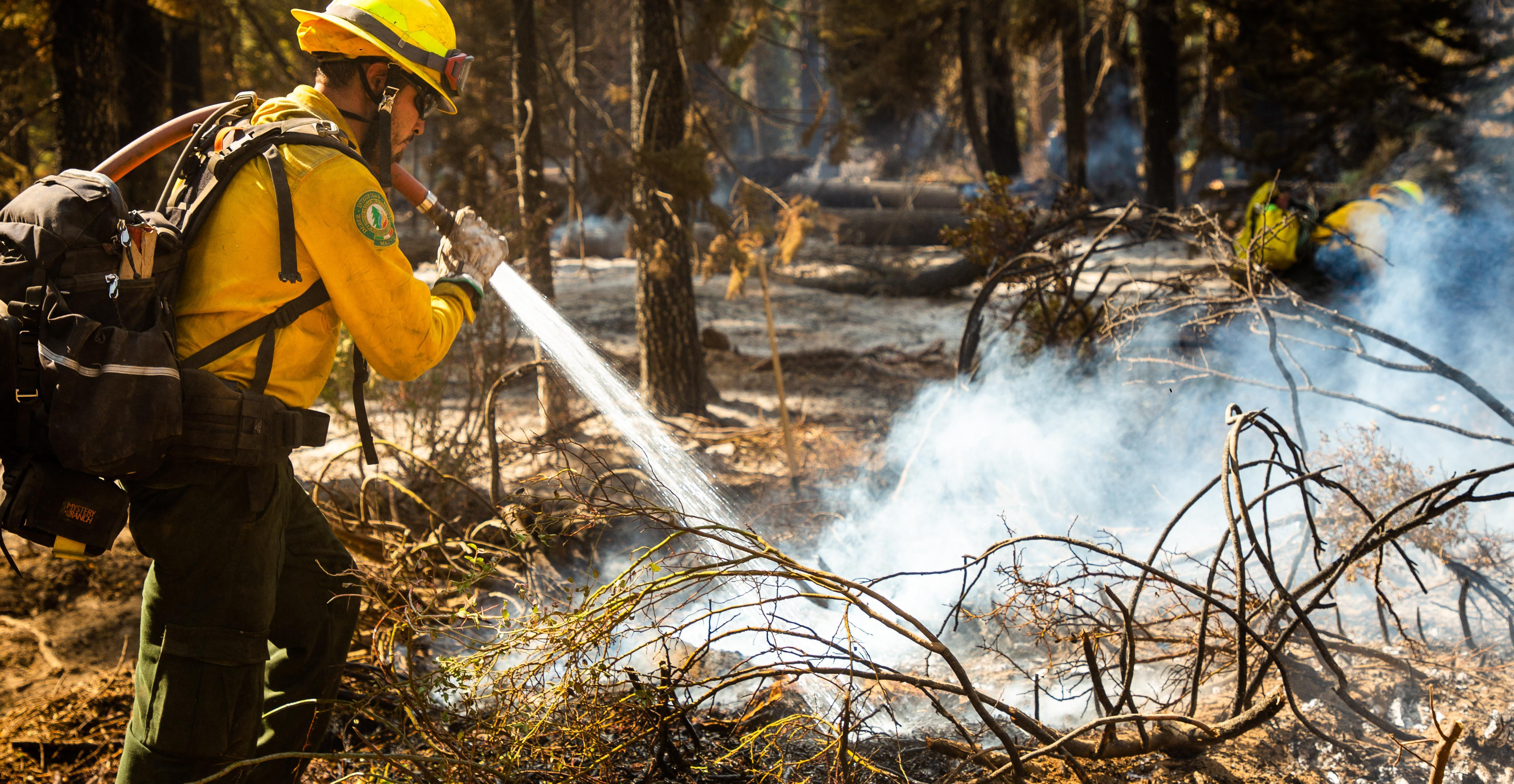 Firefighter sprays water to put out a residual hotspots