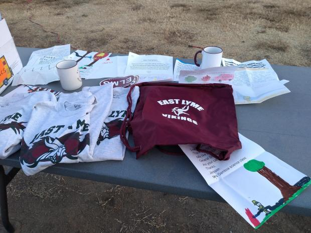 A table with colorful letters from students plus T-shirts, mugs, stickers and bags with the East Lyme Middle School Vikings logo.