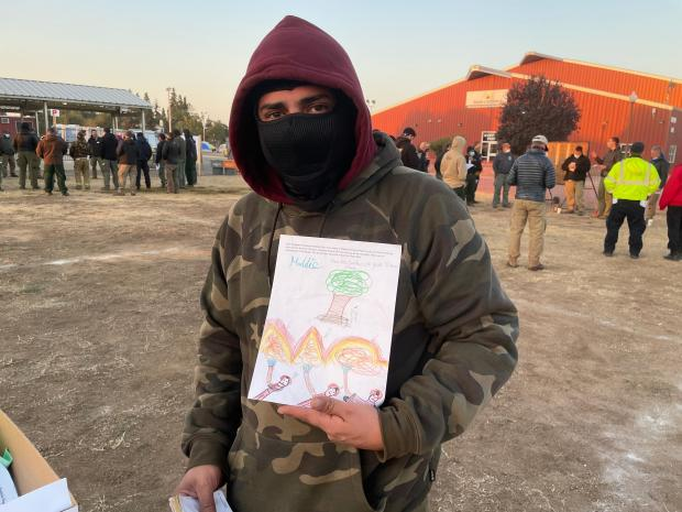 A man in  hoodie holds a letter with a student's drawing of firefighters spraying water on fire to protect a tree. In the background, other firefighters are in groups discussing their work assignments for the day.