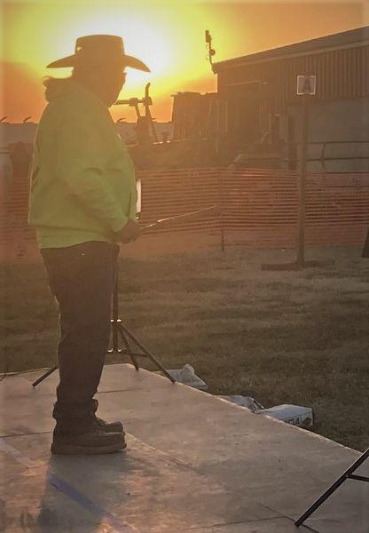 Joey Garfield stands on a stage, backlit by the rising sun. He holds a ceremonial clapstick in his right hand.
