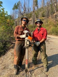 Two wildland firefighters pose with a chainsaw standing on the road.