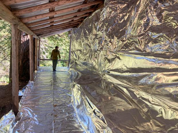 A firefighter walks across a deck covered in structure wrap.