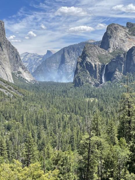 A long distance view of a glacial carved valley with light smoke above a forest floor.