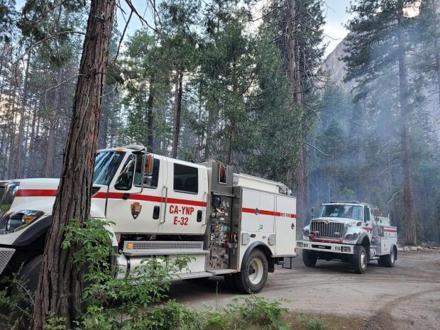 Two large fire vehicles, a fire engine and water tender, in a smoky forest.