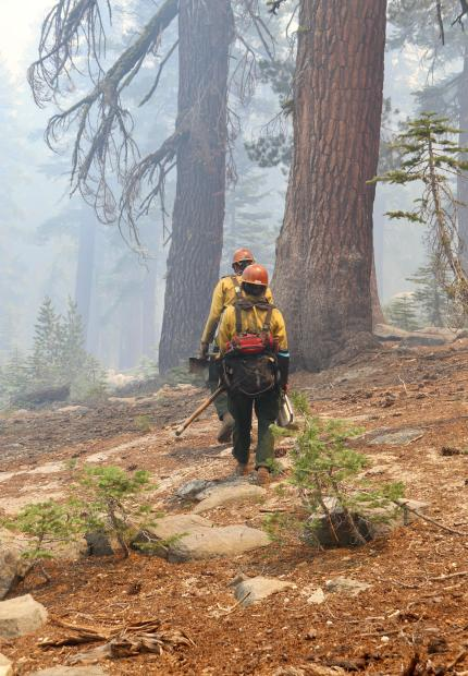 Two firefighters walk through a smoky fire carrying their gear.