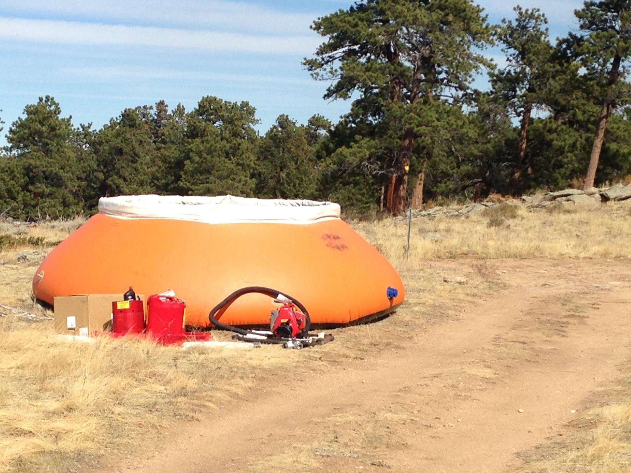A large, bright orange container holding 3,000 gallons of water sits in the grass.