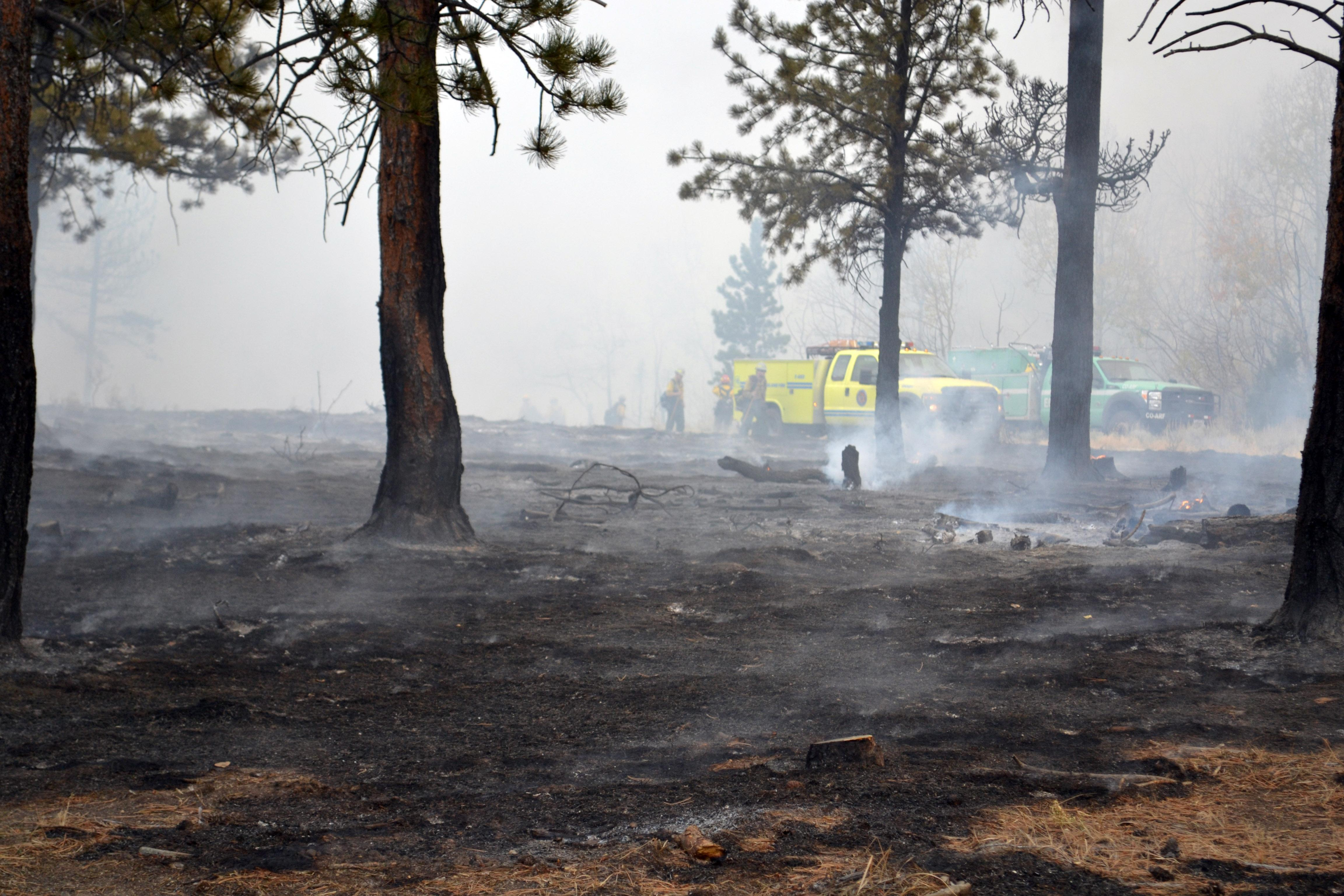 Blackened ground in the foreground with two fire engines, one yellow and one green, are in the background.