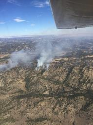 Aerial image of white smoke coming up from a tree dotted mountainous landscape.