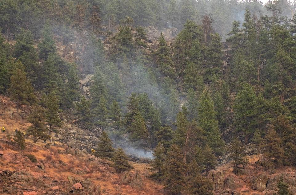firefighters work on spot fire east of CR 27