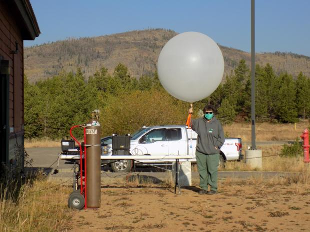 A woman holding a weather ballon before launch.