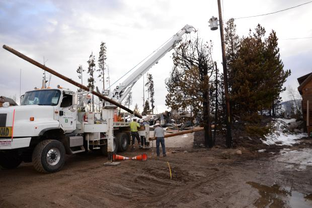 Utility workers replacing poles in the fire area