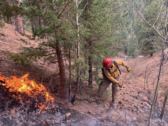 Firefighter stopping fire spread from a hot spot