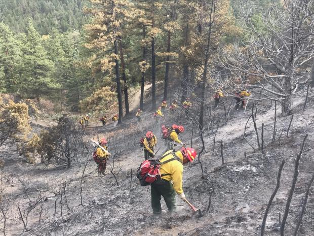 Image shows firefighters mopping up the fire in Bear Creek