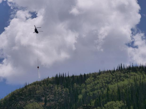 A Chinook helicopter dumps its bucket load over the Goose Creek Fire.