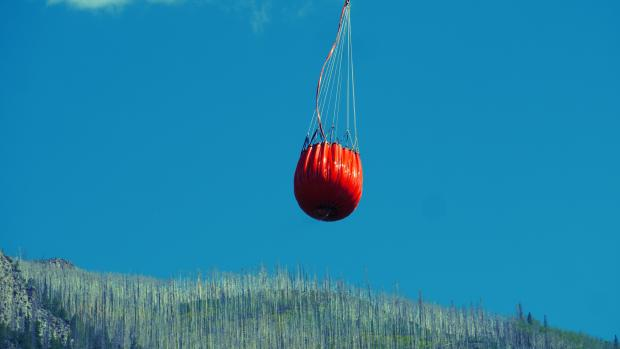 A water bucket glistens in the sun as it is hauled away from a lake.