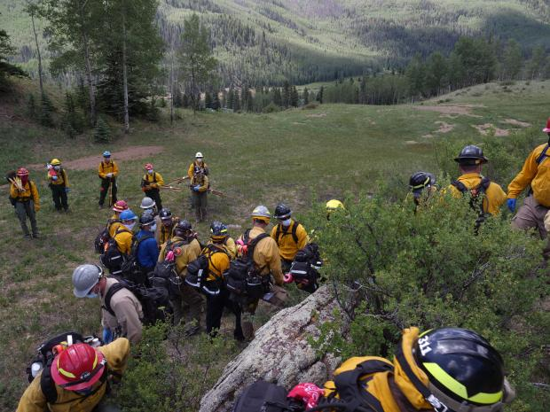 A conveyor belt carry is used to pass a mock patient from hand to hand over rocky terrain during training on the Goose Creek Fire.