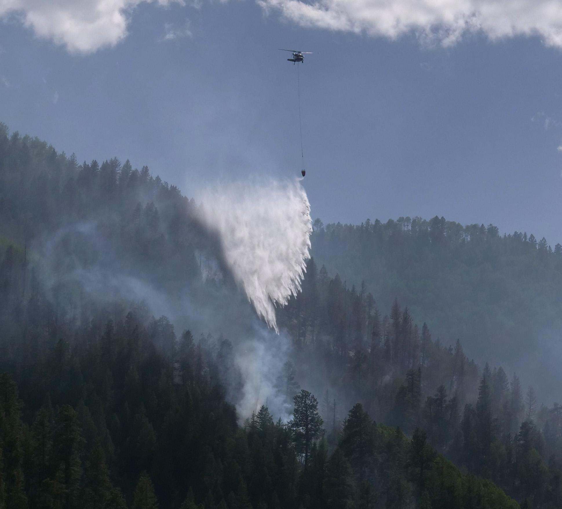 A helicopter drops a bucket of water on the Loading Pen Fire Tuesdday afternoon.