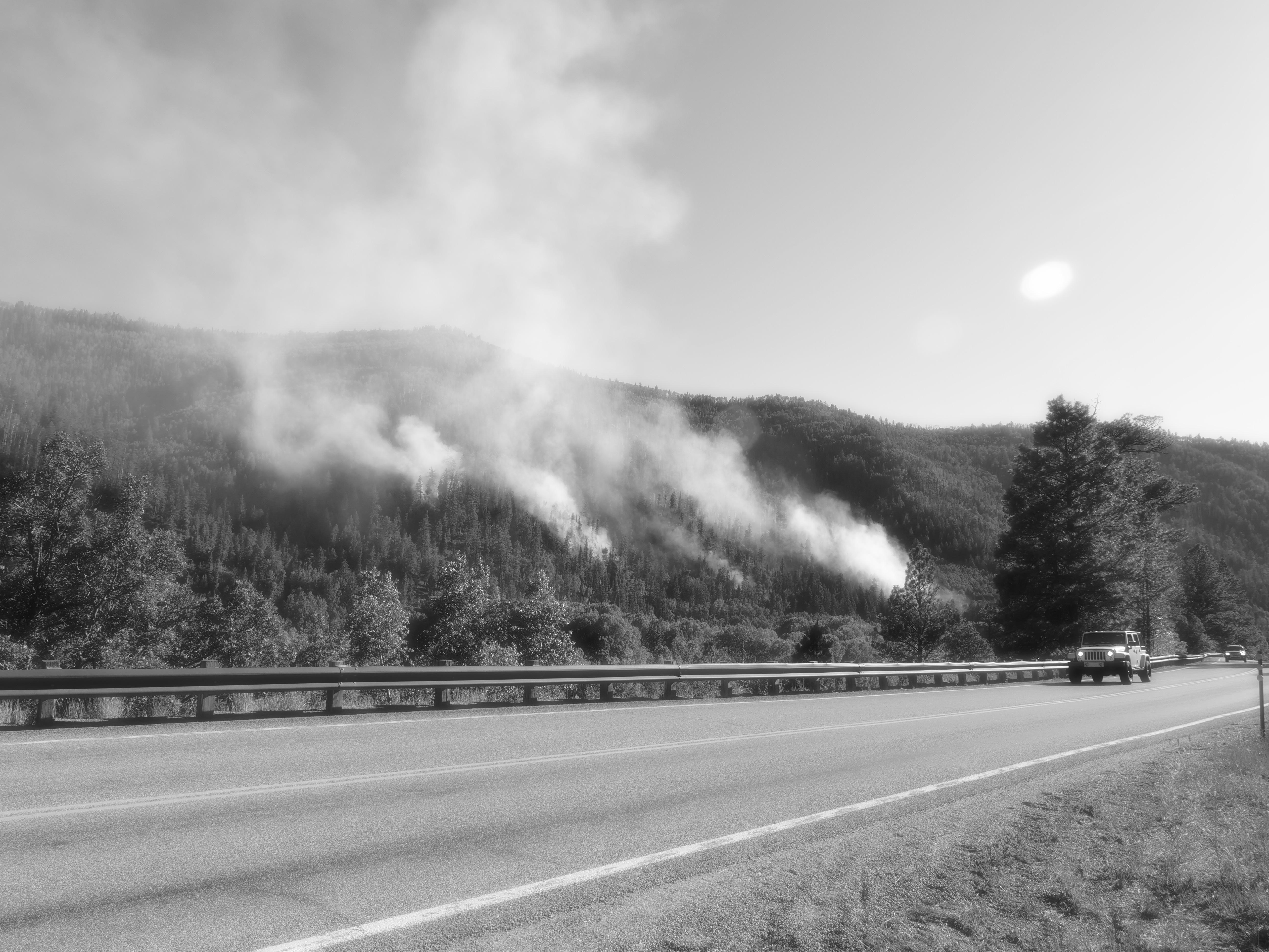 A car on Colorado Highway 145 passes by the Loading Pen Fire.