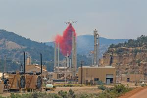 A large airplane drops fire retardant near a natural gas plant located in a canyon.