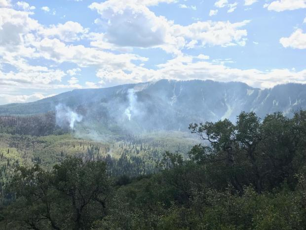 Light smoke rises from distant wooded mountain slopes.
