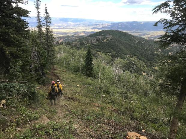 Two wildland firefighters hike down a completed fire line ona wooded slope overlooking a broad valley.