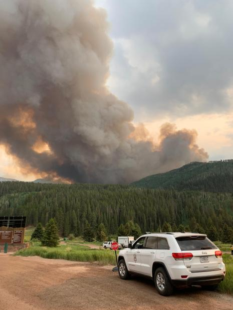 Large, dark smoke plume shows the activity on the Sylvan Fire. A forest service vehicle is in the foreground.