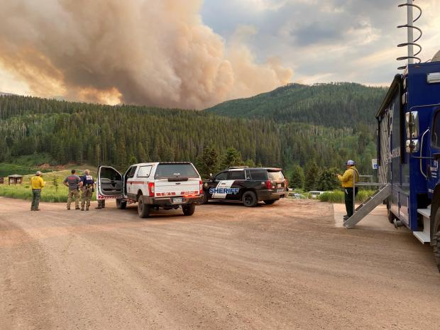 Large smoke plume seen with vehicles in the foreground. The picture is from Sylvan Lake State Park.