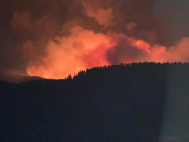 A night photo showing the orange glow of the Sylvan Fire
