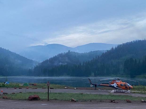 A small helicopter sits on the ground in front of Sylvan Lake on an overcast day.