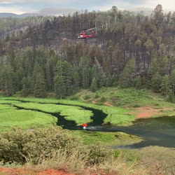 K-Max helicopter finishes loading its bucket and begins to move away from a lake surrounded by mountains