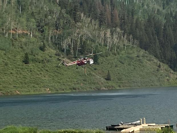 a large skycrane helicopter approaches a lake at low level in order to get water