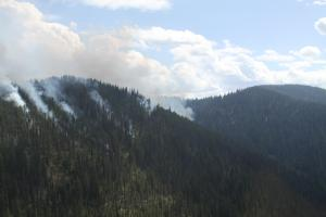 Smoke rises from midslope to the ridge as the fire burns slowly downslope.