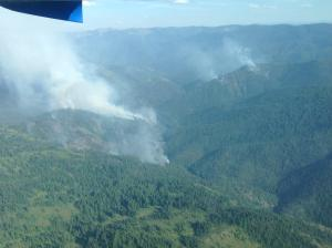 Aerial view of smoke rising from the ridge to the valley bottom on the left with another area of smoke showing across the drainage.