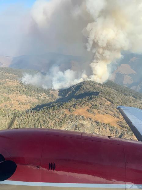 A smoke column rises in the distance in this photograph taken of the Bryan Mountain fire by airplane. The red body of the airplane is visible in the foreground.