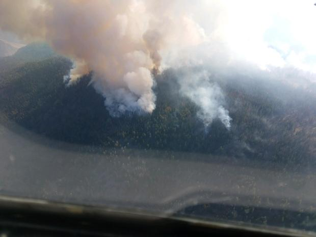 A smoke column rises from the Bryan Mountain fire