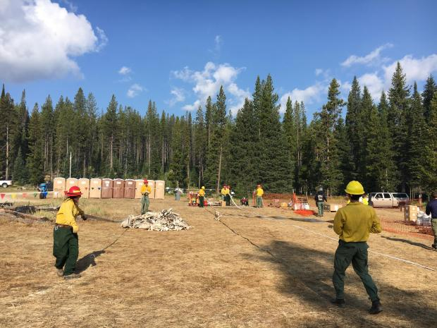 Members of Caribou-Targhee Camp Crew 1 begin rolling hose used during the Nethker Fire.