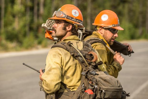 A Mt. Taylor Hotshot looks back toward the main body of the Nethker Fire on the evening of Aug. 7 shortly after the fire moved across the Burgdorf/French Creek Road.
