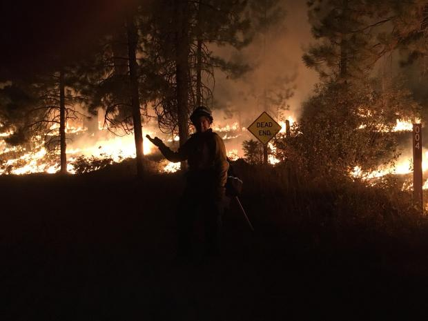 Fire burning in timber with shadow of a fire fighter in the center