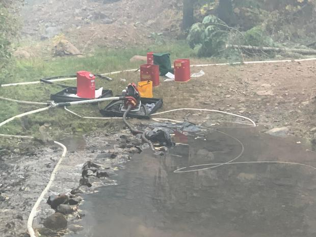 Several pumps with hoses going into a pond and coming out of the pumps.