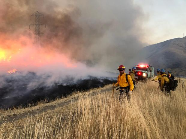 fire fighters, fire, black ground and unburned vegetation with smoke in the background.