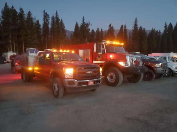 Fire engines with lights on, on a dirt road with trees in the background